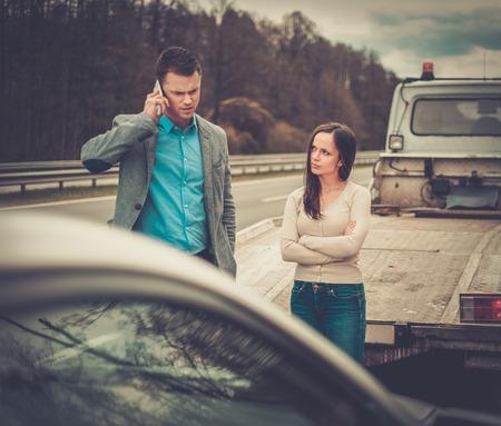 towing: Couple near broken car on a roadside