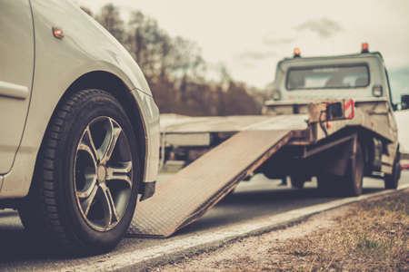 camioneta pick up: Cargando coche roto en un camión de remolque en una carretera Foto de archivo