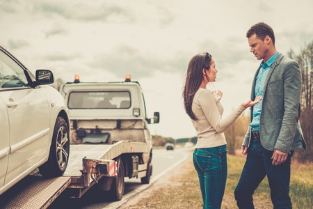 rescue people: Couple near tow-truck picking up broken car Stock Photo