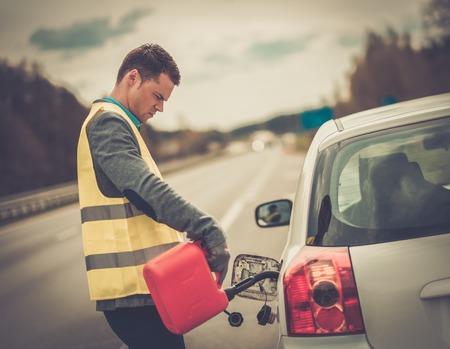 roadsides: Man refuelling his car on a highway roadside