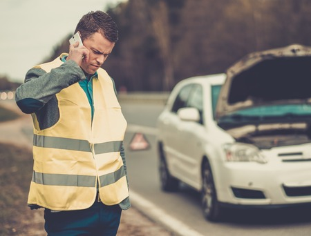 towing: Man calling car towing service on a highway roadside
