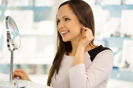 silver jewellery: Woman trying on earrings in a  jewellery