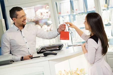 pagando: Cliente feliz mujer en una tienda de joyas