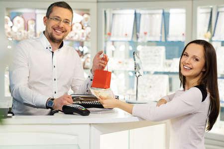 vendedores: Mujer que paga con dinero en efectivo en la tienda de joyas