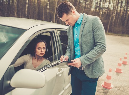 passed test: Driving instructor and woman student in examination area