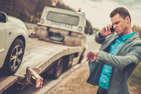truck repair: Man calling while tow truck picking up his broken car