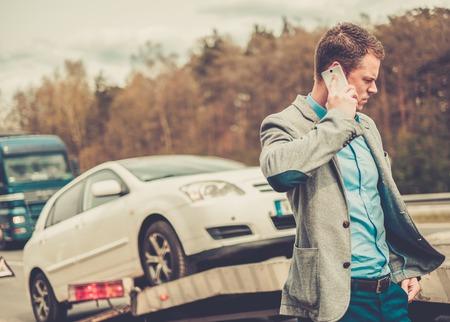 pickup truck: El hombre que llama mientras gr�a recoger su coche roto Foto de archivo