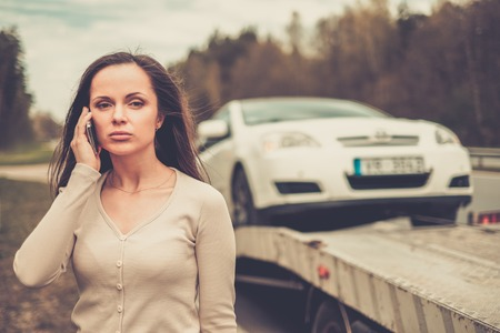 automobile insurance: Woman calling while tow truck picking up her car