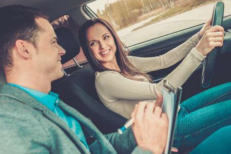hombre conduciendo: Conducir instructor y estudiante mujer en el coche de examen