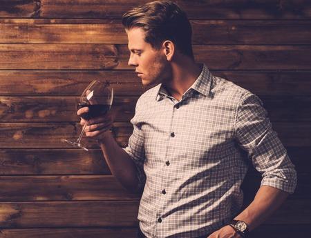 beau jeune homme: Man d�gustation de vins dans l'int�rieur rurale de chalet Banque d'images