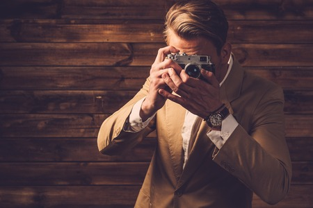 Stylish man with retro camera in rural cottage interior