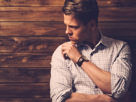 man shirt: Handsome man wearing checkered  shirt in wooden rural house interior