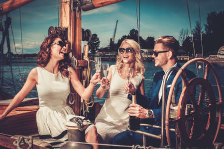 Stylish wealthy friends having fun on a luxury yacht. Stock Photo
