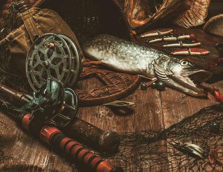 pescando: Herramientas de la pesca y el lucio fresco en una mesa de madera