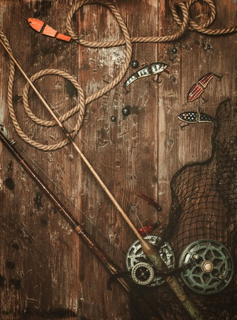 a freshwater fish: Fishing tools on a wooden background