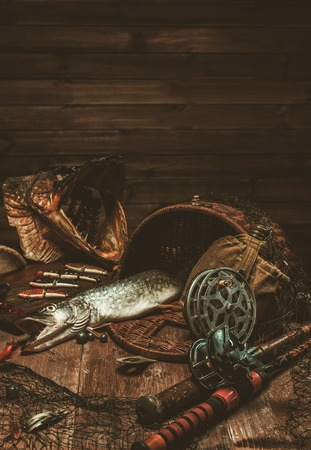 pike: Fishing tools and fresh pike on a wooden table Stock Photo