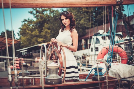 private party: Stylish wealthy woman on a luxury wooden regatta Stock Photo