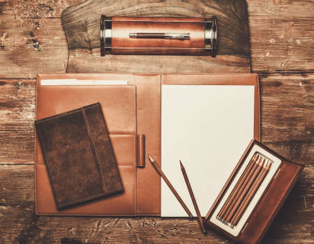 person writing: Luxurious writing tools on a wooden table