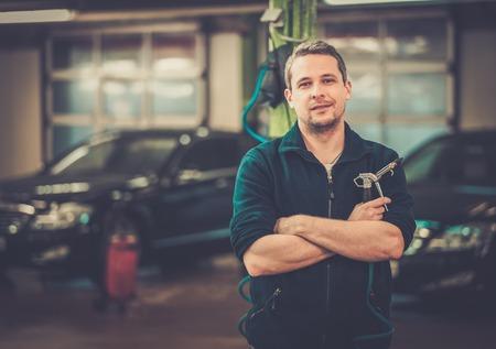 persona alegre: Trabajador feliz en un lavadero de autos Foto de archivo