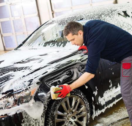 El trabajador del hombre lavado de coches de lujo con esponja en un lavadero de autos