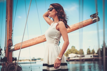 Stylish wealthy woman on a luxury wooden regatta Stock Photo