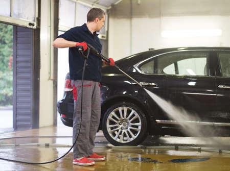 manos limpias: El trabajador del hombre lavado de coches de lujo en un lavadero de autos Foto de archivo