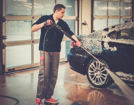 autolavaggio: L'uomo lavoratore lavaggio auto di lusso in un autolavaggio Archivio Fotografico
