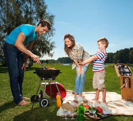 chorizos asados: Familia joven que se prepara salchichas en una parrilla al aire libre