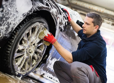 wet men: Man worker washing cars alloy wheels on a car wash