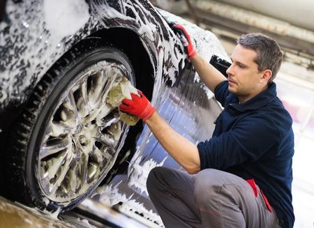 alloy: Man worker washing cars alloy wheels on a car wash