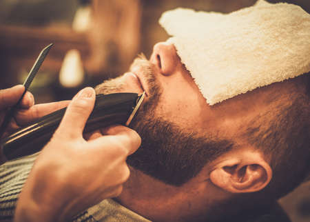 barber: Client during beard and moustache grooming in barber shop