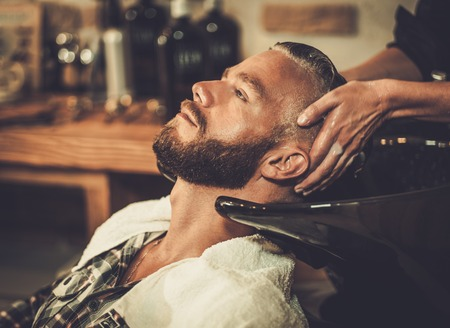 barber: Hairstylist washing clients hair in barber shop
