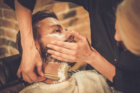 blades: Client during beard shaving in barber shop Stock Photo