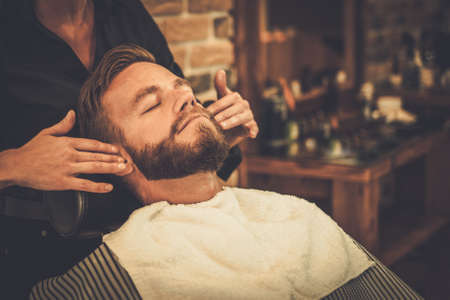 barbero: Hairstylist aplicar loción después del afeitado en barbería
