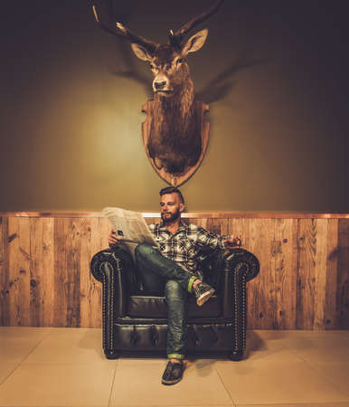 Middle-aged hipster reading newspaper on leather chair will glass of whiskey Stockfoto