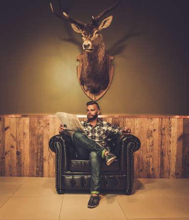 cazador: Periódico de la lectura del inconformista de mediana edad en silla de cuero cristal voluntad de whisky