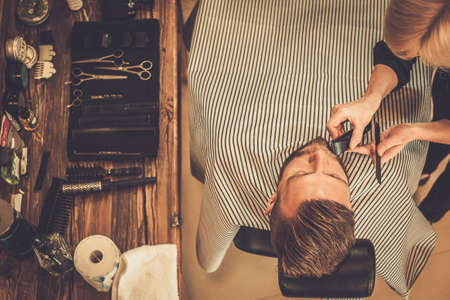 barbero: Cliente durante la barba y el bigote acicalado en barbería Foto de archivo