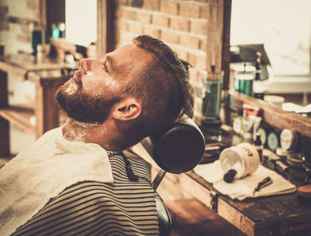straight man: Client during beard shaving in barber shop Stock Photo