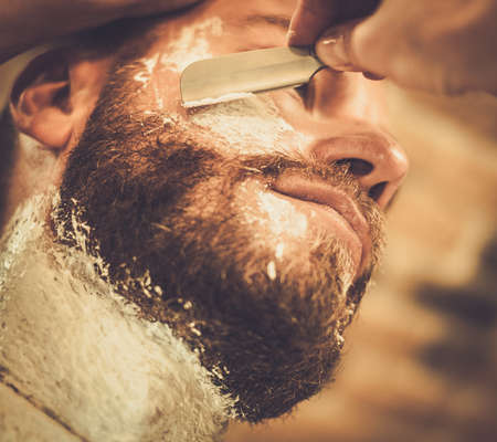 straight razor: Client during beard shaving in barber shop Stock Photo