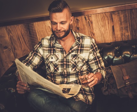 flannel: Middle-aged hipster reading newspaper on leather sofa in barber shop Stock Photo
