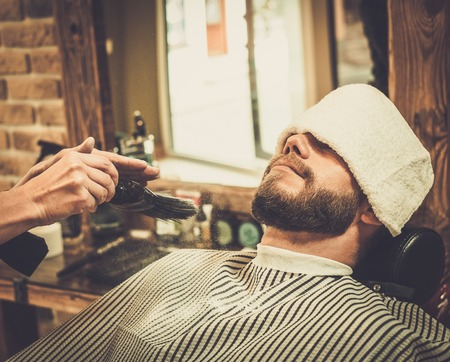barber shave: Hairstylist applying  beard powder in barber shop