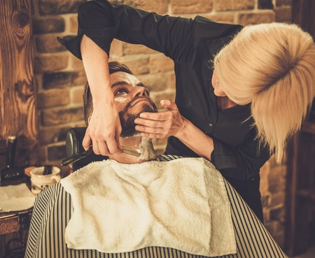 barber: Client during beard shaving in barber shop Stock Photo