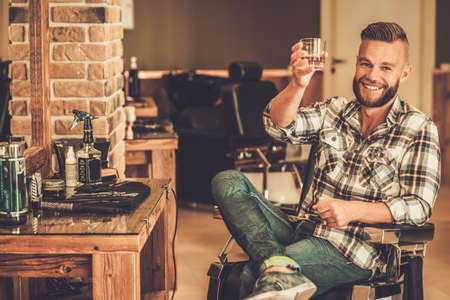 hairdressers: Happy client in barber shop will glass of whiskey