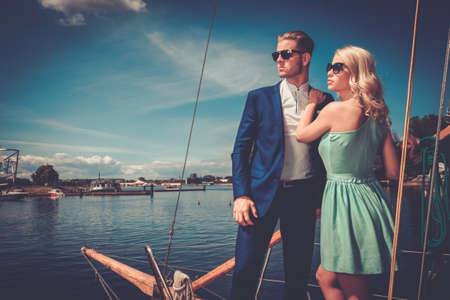 boat party: Stylish wealthy couple on a luxury yacht