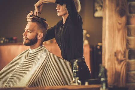beard woman: Client visiting hairstylist in barber shop Stock Photo