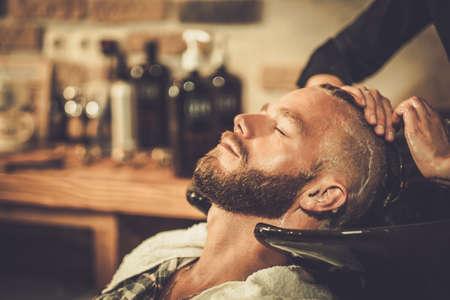 champú: Pelo Hairstylist del cliente lavado en barbería Foto de archivo