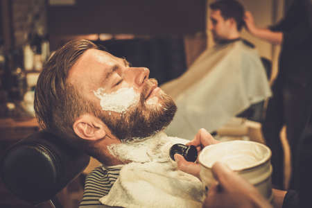 during: Client during beard shaving in barber shop Stock Photo