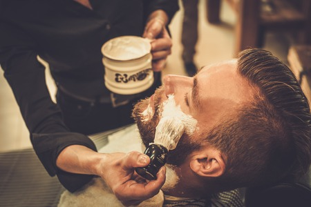 hairdressers: Client during beard shaving in barber shop Stock Photo