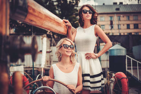 luxury lifestyle: Stylish wealthy women on a luxury yacht Stock Photo