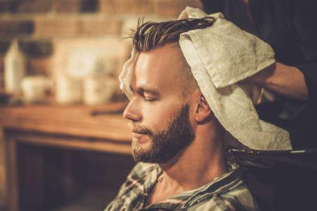 Les cheveux de coiffeur laver client dans la boutique de barbier